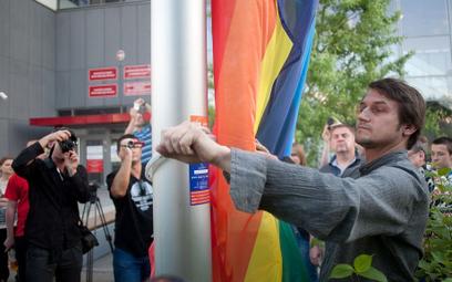 Piotr Guział podnosi tęczową flagę na maszcie przy urzędzie dzielnicy Ursynów - 2011 rok