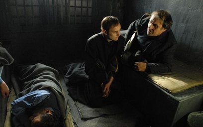 Ks. Popiełuszko (Adam Woronowicz) słucha opowieści współwięźnia (Ryszard Doliński)
