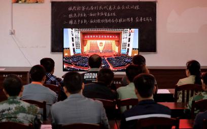 Mieszkańcy wioski na południu Chin oglądają wystąpienie Xi Jinpinga, w którym ogłasza pokonanie bied