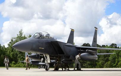 Lotnicy różnych specjalności tankują samolot myśliwsko-bombowy F-15E Strike Eagle, którego pilot cał