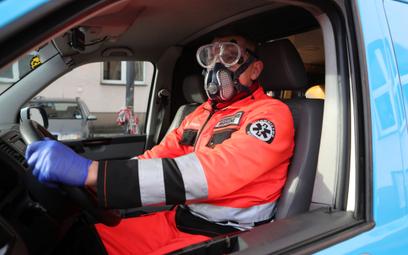 Ratownik medyczny w odzieży ochronnej w karetce pogotowia