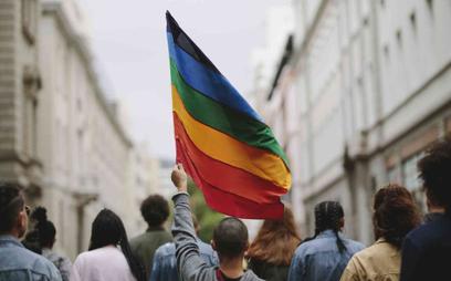 Mężczyzna unosi w górę tęczową flagę (zdjęcie ilustracyjne)