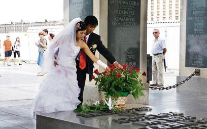 Tożsamość narodowa na ostro: wietnamska młoda para składa kwiaty na Grobie Nieznanego Żołnierza. Fot