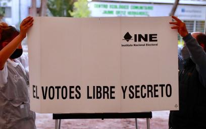 """Członkowie jednej z komisji wyborczych w Meksyku ustawiają parawan z hasłem """"Głosowanie jest wolne i"""