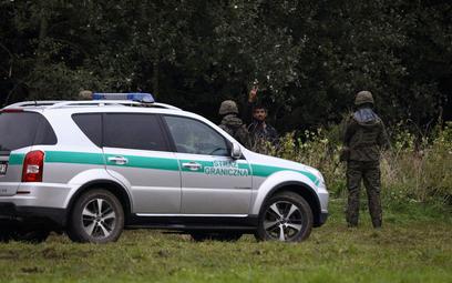 Samochód Straży Granicznej obok koczowiska uchodźców na granicy z Białorusią