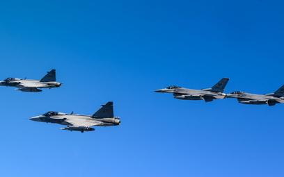 Szwedzkie samoloty wielozadaniowe Saab JAS-39C Gripen w locie w szyku z amerykańskimi F-16C podczas
