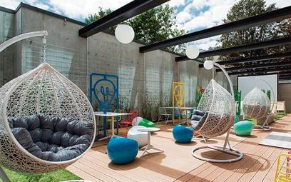 Idea Hub w Warszawie ma wewnętrzne patio,  w którym ulokowano stoliki  do pracy, kanapy, fotele, ham