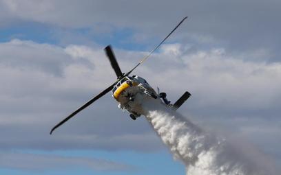 Wielozadaniowy śmigłowiec pożarniczy Sikorsky S-70i Firehawk podczas zrzutu środka gaśniczego. Fot./