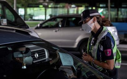 Policjanta w Madrycie żąda od kierowcy dokumentu uprawniającego go do opuszczenia dzielnicy, fotogra