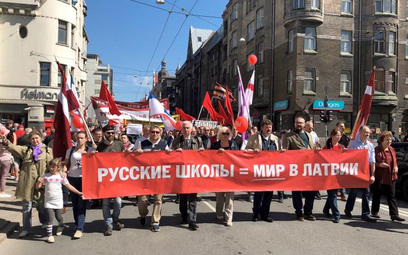 """Protestujący w Rydze maszerowali z transparentem: """"Rosyjskie szkoły oznaczają pokój na Łotwie""""."""