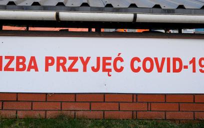 """Tablica z napisem """"Izba przyjęć COVID-19"""" przed szpitalem w Warszawie"""